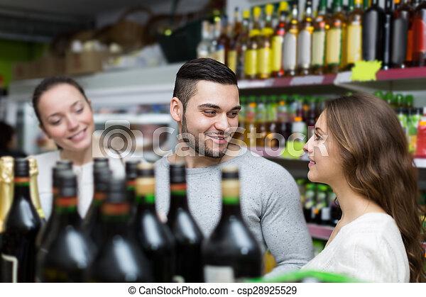 shoppers choosing bottle of wine at liquor store - csp28925529
