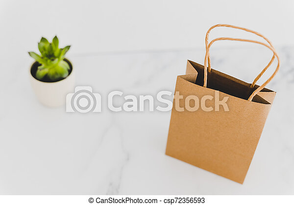 shopping bag on marble table top with succulent in the background - csp72356593