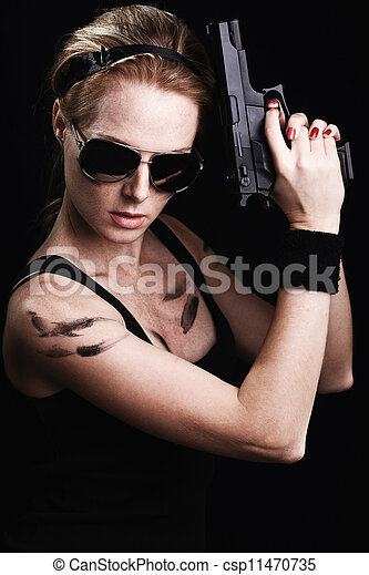 Shot of a sexy military woman posing with gun - csp11470735