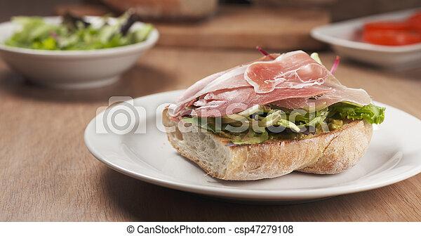 shot of speck put on ciabatta bread preparing sandwich - csp47279108