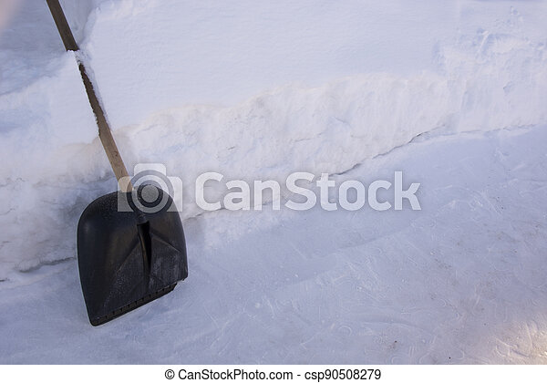 Shovel in the snow. High snowdrifts. Raking away the snow in the garden. There is a lot of snow in the garden in winter. - csp90508279