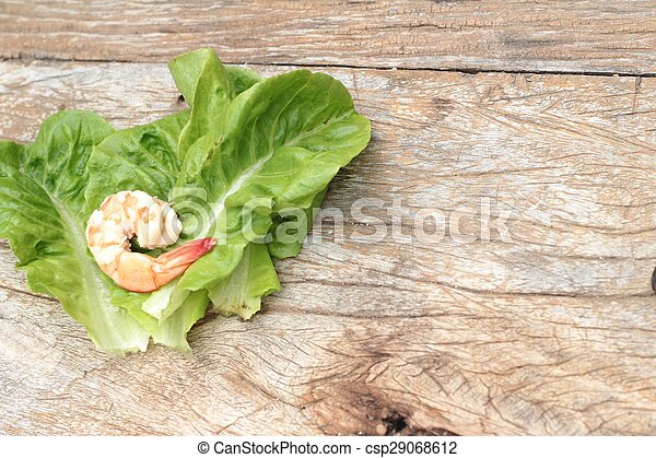 Shrimps with vegetables green leaves on wood background. - csp29068612