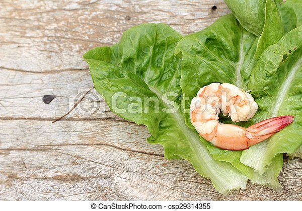 Shrimps with vegetables green leaves on wood background. - csp29314355