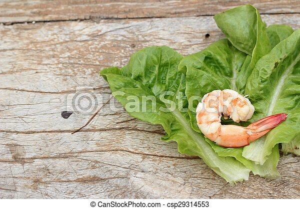 Shrimps with vegetables green leaves on wood background. - csp29314553