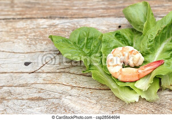 Shrimps with vegetables green leaves on wood background. - csp28564694
