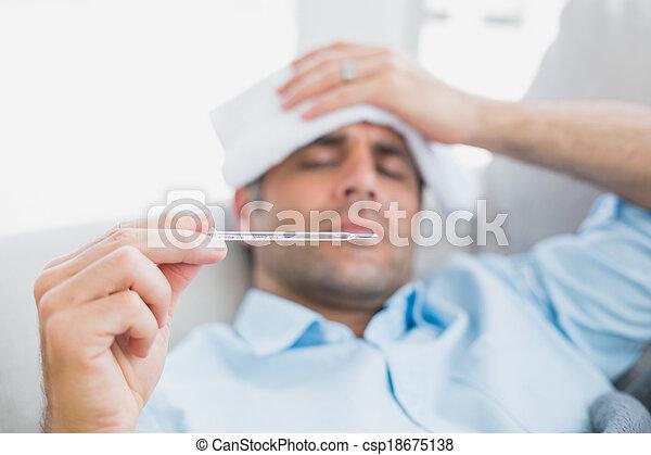 Sick man lying on sofa checking his temperature - csp18675138