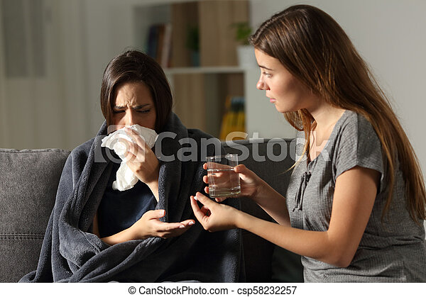 Sick woman and her friend giving painkiller pill - csp58232257
