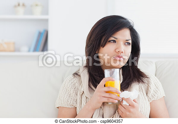 Sick woman holding a glass of orange juice - csp9604357