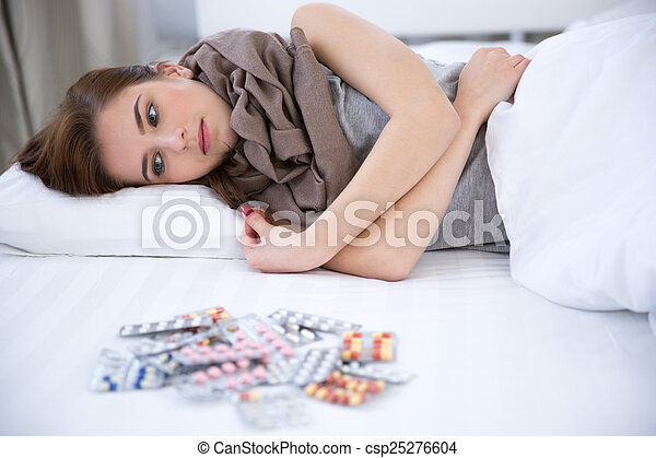 Sick young woman lying on the bed at home - csp25276604