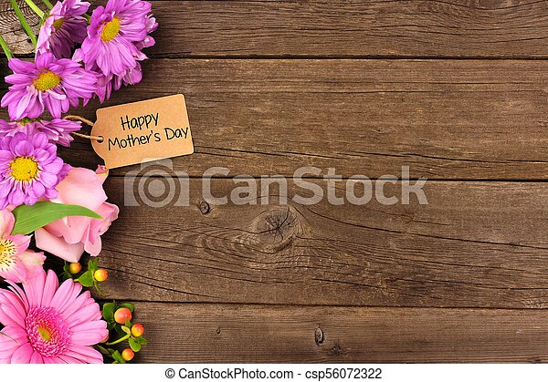 Side border of flowers with Mothers Day gift and tag against rustic wood - csp56072322