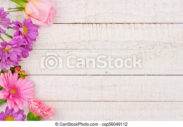 Side border of pink and purple flowers against white wood - csp56049112
