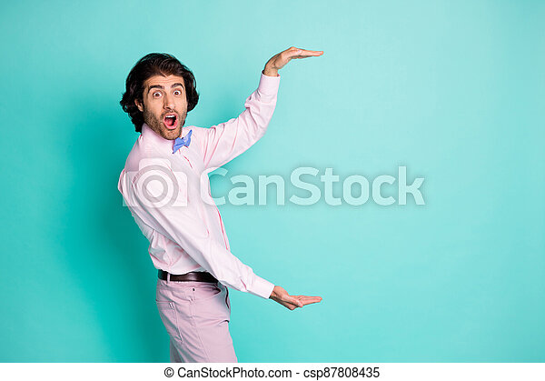 Side photo of cheerful brown wavy hair man wear pink outfit measure empty space two hands isolated teal color background - csp87808435