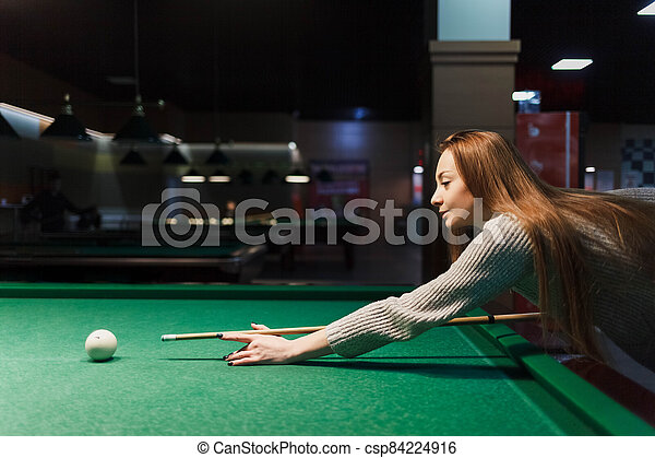 side view at the woman plays billiards in a dark pub - csp84224916
