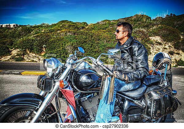 side view of a biker on a classic motorcycle - csp27902336