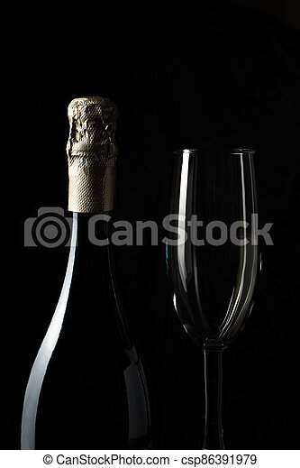 Side view of a champagne bottle and glass on a black background. - csp86391979