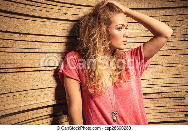 side view of a cool fashion woman holding her hair up and looks away