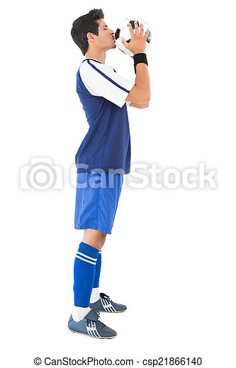 Side view of a handsome football player kissing ball - csp21866140
