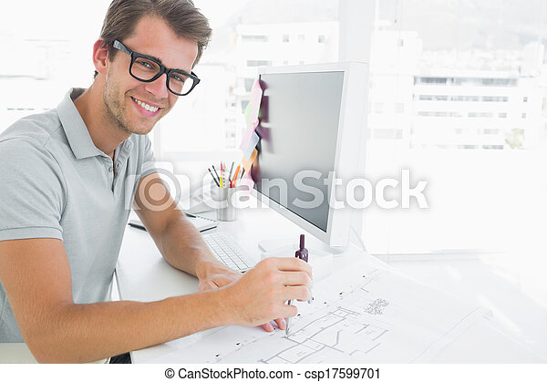 Side view of a smiling young man using compass - csp17599701