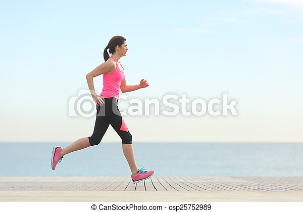 Side view of a woman running on the beach - csp25752989