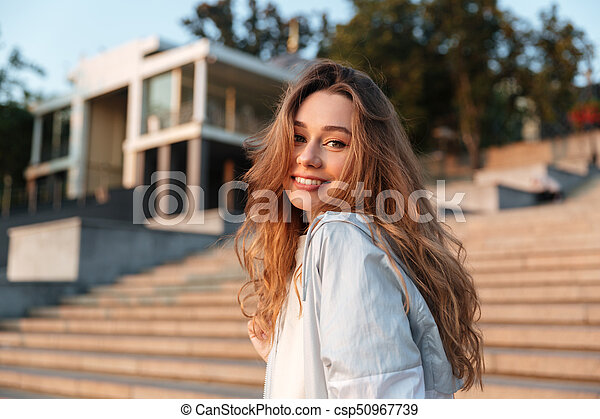 ca674b7219 Side view of happy brunette woman in autumn clothes posing outdoors ...