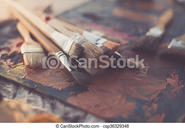Side view of pallet with oil paint brushstrokes under paintbrush set in an art studio. - csp36329348