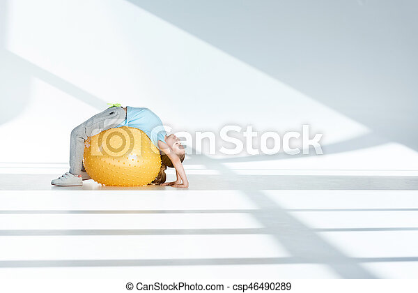 Side view of sporty little girl exercising on fitness ball - csp46490289