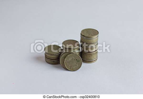 Side view of stacks of coins increasing in height, on white studio  background