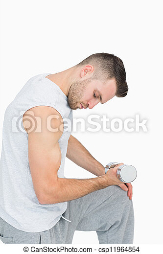 Side view of young man exercising with dumbbell - csp11964854