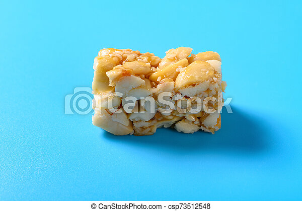 side view peanut nougat close up on blue background - csp73512548