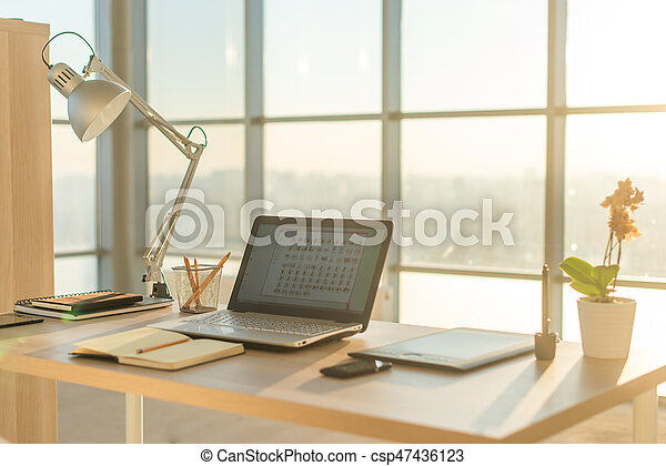 Side view picture of studio workplace with blank notebook laptop. Comfortable work table & Side view picture of studio workplace with blank notebook laptop ...