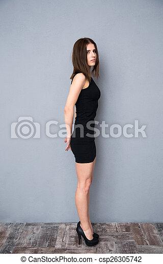 Side View Portrait Of A Cute Woman In Black Dress Full Length