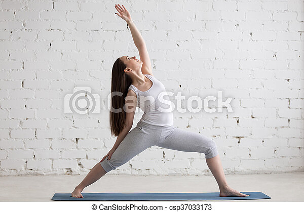 Side view portrait of happy woman doing Reverse Warrior Pose - csp37033173