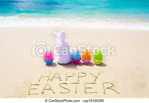 "Sign ""Happy Easter"" with bunny and color eggs on the beach - csp19165390"