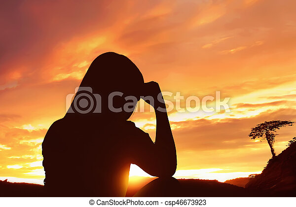 silhouette depressed woman sitting alone on top of the mountain at