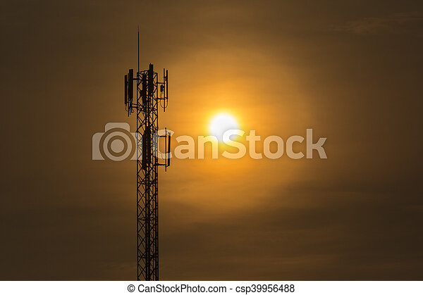 Silhouette electric pole back lit by the afternoon sun - csp39956488