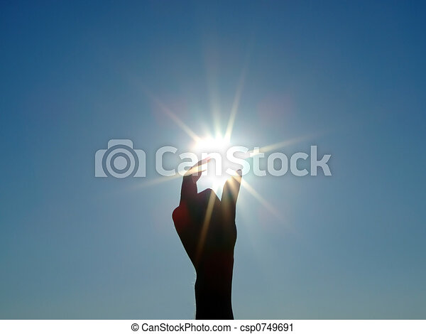 Silhouette of a female hand, the blue sky and the bright sun 2 - csp0749691