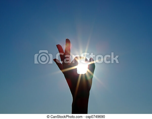 Silhouette of a female hand, the blue sky and the bright sun - csp0749690