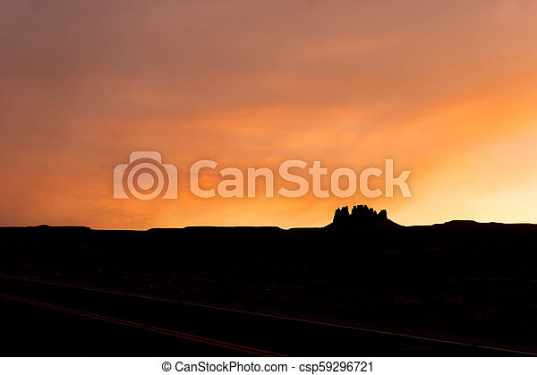 silhouette of a rock butte in the desert at sunset - csp59296721