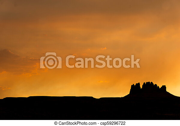 silhouette of a rock butte in the desert at sunset - csp59296722