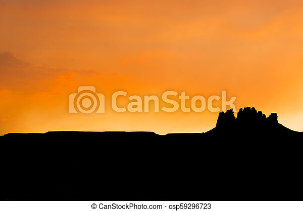 silhouette of a rock butte in the desert at sunset - csp59296723