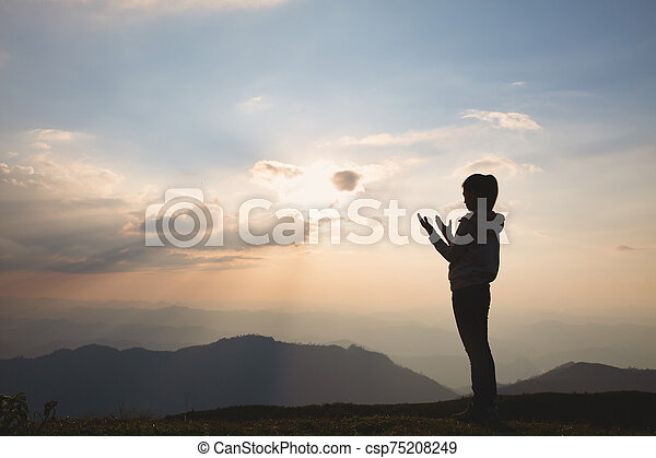 Silhouette of a woman with hands raised in the sunset concept for religion, worship, prayer and praise, Religious concepts - csp75208249