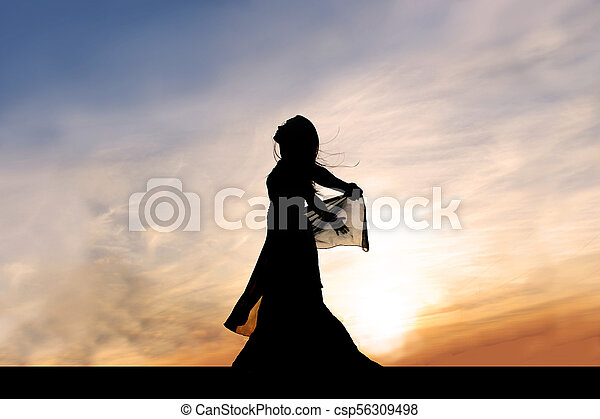 Silhouette of Beautiful Young Woman Outside at Sunset Praising God - csp56309498