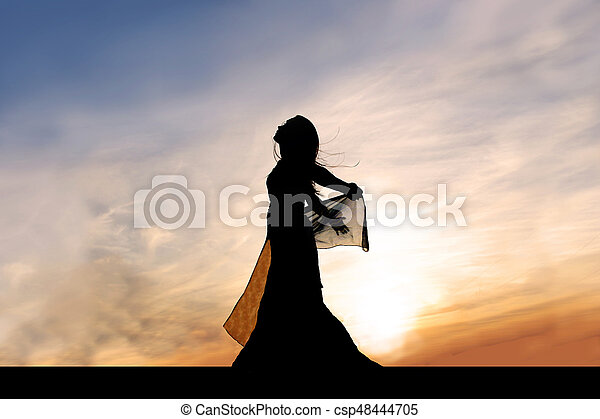 Silhouette of Beautiful Young Woman Outside at Sunset Praising God - csp48444705