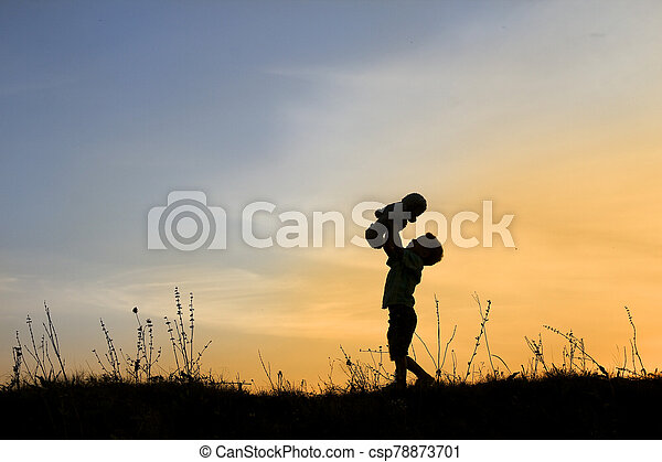 silhouette of child with bear on sunset - csp78873701
