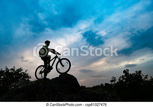 Silhouette of Cyclist with Mountain Bike on Rock at Sunset. Extreme Sports and Enduro Cycling Concept. - csp61027476