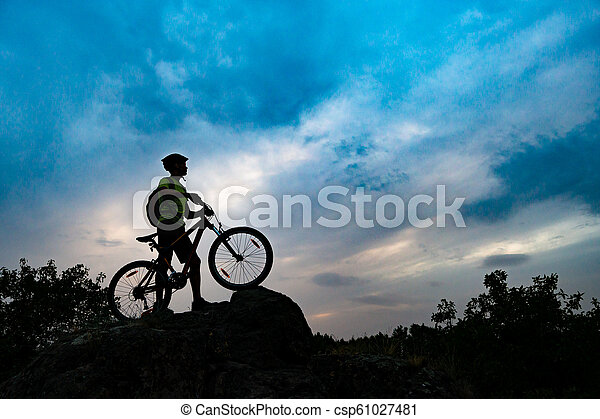 Silhouette of Cyclist with Mountain Bike on Rock at Sunset. Extreme Sports and Enduro Cycling Concept. - csp61027481