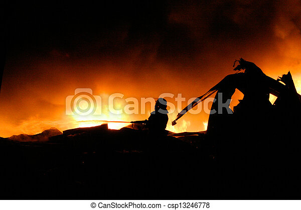 Silhouette of Firemen fighting a raging fire - csp13246778