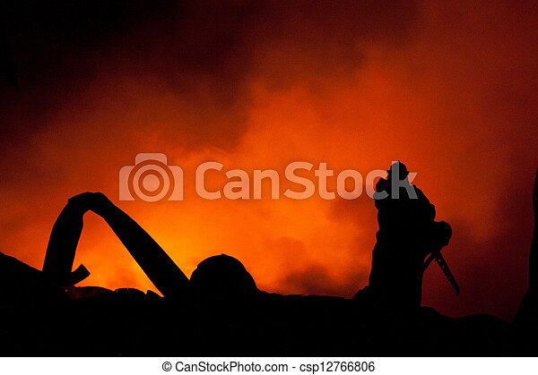 Silhouette of Firemen fighting a raging fire with huge flames  - csp12766806