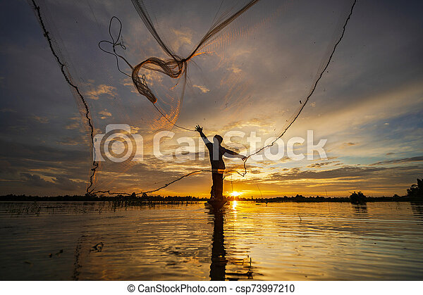 Silhouette of Fisherman on fishing boat with net on the lake at sunset, Thailand - csp73997210
