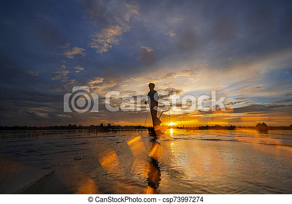 Silhouette of Fisherman on fishing boat with net on the lake at sunset, Thailand - csp73997274
